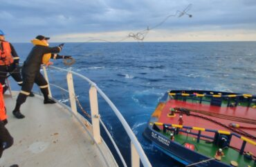 Indian Coast Guard officials connecting the burning MT New Diamond oil tanker to a tug boat